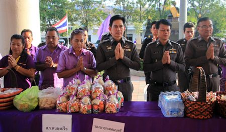 Pol. Col. Pramote Ngampradit (3rd right), superintendent of Nongprue Police Station, and Pol. Col. Thanayot Yungyuen (2nd right), senior investigation officer for Nongprue, present alms along with fellow officers and spouses.