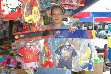 Nongrak shows some of her water guns for youngsters. She has been taking orders from football lovers for particular football teams.