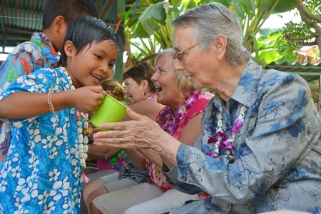 """Children perform the """"rod nam dam hua"""" ceremony, pouring scented water into the palms of elders."""