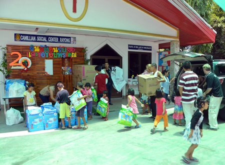 Camillian Social Center Rayong staff helps to carry the necessities donated by the Pattaya Sport Club.