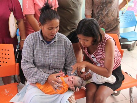 Motherly women crowd around the abandoned child. Wilai Tonelung (right) found the infant lying in a foam box at her family's banana plantation in Sattahip.
