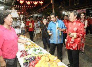 Former Culture Minister Sonthaya Kunplome (center) tastes some Chinese desserts at the opening of the fair.