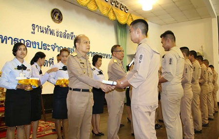Rear Adm. Chatchawal Meesawad presents a certificate to one of 112 outgoing seamen at Sattahip Naval Base.