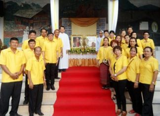 Members of the parish council stand in cordon in front of the pictures and relics of the two popes. In the background left is Rev. Peter Suraporn Suwichakorn.