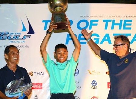 Suthon Yampinid lifts the 40-year old Thailand Optimist National Championship trophy, presented by Rear Admiral Sunan Monthardplin, Yacht Racing Association of Thailand and President of Junior Sailing Squadron (left), and past winner Mark Tchelistcheff (right).