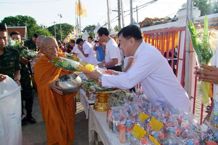 Chonburi residents offer alms to a procession of monks in the morning.