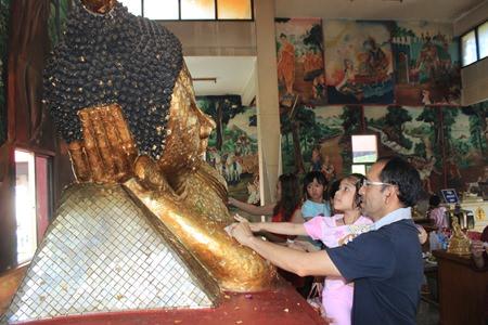 Devout Buddhists gathered to gild the Buddha statue at Wat Sutthawas.