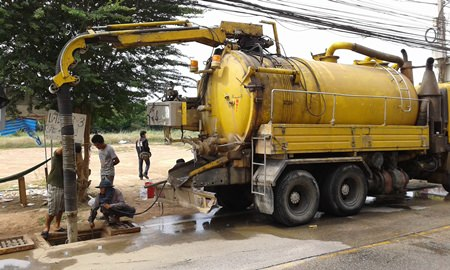Workers from Mario Engineering Ltd., use vacuums and other equipment to suck rubbish, plastic bags, mud and other objects out of the drains along Soi Khao Talo.