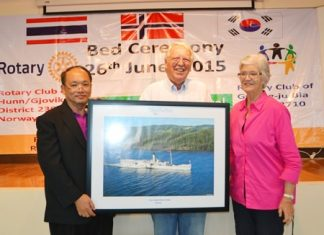 As part of their matching donation, Helge Holst and his wife Brita present hospital director Dr. Sukit Pungketsunthorn with a picture of the Norwegian ship Skibladner.