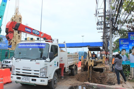 Workers begin digging holes for the new footbridge foundation piles near the Bangjak gas station.