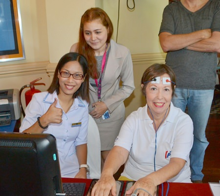 PCEC member Judith Edmonds receives a free scan from the Surecell staff using their EIS Bio-Scanner which helps to identify what ails you.