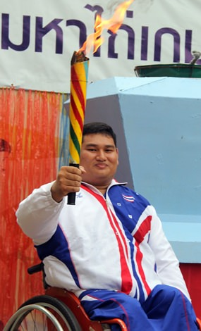 Former Paralympian weightlifter Prakit Thongsang carries in the flame to start the Mahathai Games 2015.
