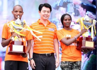 Pattaya Marathon 2015 winners, Onesmus Muasya (left) and Viola Jepchir Kimeli (right), both of Kenya, hold their HM King's Cup trophies as they pose for photos with former MP Poramate Ngampichet.