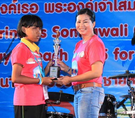 Pattaya Sports Club Charity Chair Noi Emmerson (right) hands over a trophy to a young athlete.