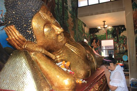 After adding her gold foil to the Buddha Statue at Luang Poh Tho, Wat Suttawas, she prays for the benefit of everyone in the world.