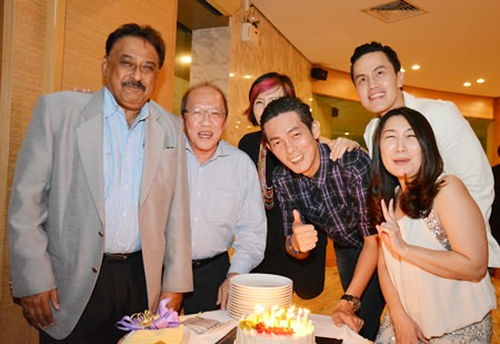 Friends gather around Sanphet 'Mod' Suphabuansathien as he prepares to blow out the candles on his birthday cake.