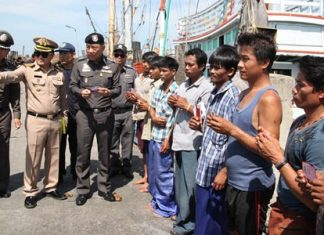 Workers aboard fishing vessels currently at port in Samae San hold up their legal papers and IDs for the police entourage to inspect.