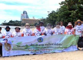 Australian tourist Bob Borgiani (far right) poses on Pattaya Beach with workers from the clean-up team sent by city hall, Wednesday, August 5.