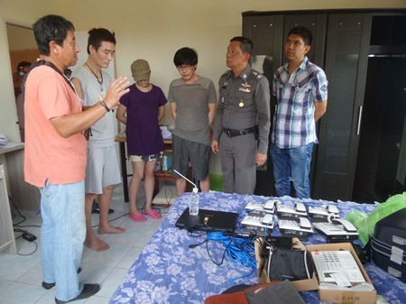 Jonggeun Kim, Duri Kim, and Kisoo Oh (standing 2nd left to 3rd right) have been arrested on immigration offenses while police look into their operating a telephone-fraud call center in Pattaya.
