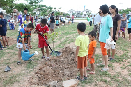 Youths and residences of the government housing village in Nernplabwan plant trees to spruce up the surroundings and help prevent erosion during the rainy season.