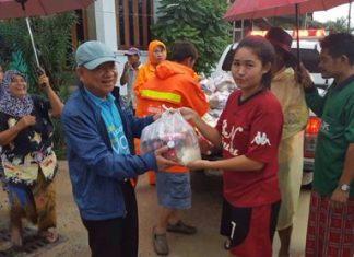 Nongprue Mayor Mai Chaiyanit (front left) hands out supplies to flood victims in the Nong Yai area.