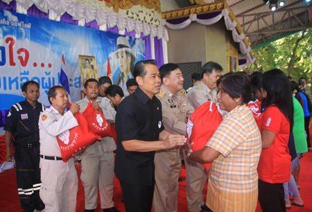 (L to R) Project Director Manus Nonuch, Chonburi Deputy Governor Phawat Lertmukda, and Banglamung District Chief Chakorn Kanjawattana help distribute 500 royal emergency bags to flood victims from HRH Princess Ubolratana.