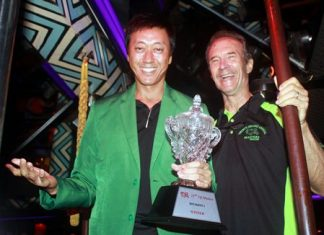 2015 TQ Masters champion Gene Connor (left) dons the green jacket as he accepts the Division 1 trophy from Lewis 'Woody' Underwood (right) at the Tahitian Queen rock 'n' roll bar on Friday, Oct. 16. For a full report on the 22nd annual TQ Masters golf tournament.