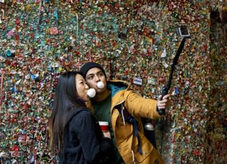 """Jessica Wang, left, and Michael Teylan, both of Los Angeles, use a selfie stick at Seattle's """"gum wall"""" at Pike Place Market, Monday, Nov. 9, 2015. (AP Photo/Ted S. Warren)"""