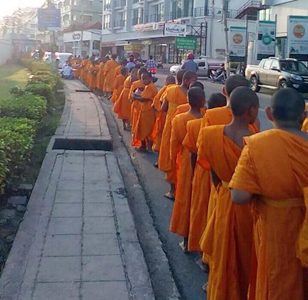 Young monks line the street to accept alms marking Auk Phansa, the end of Buddhist Lent.