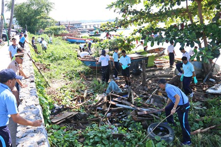 Sailors and officers join community residents in cleaning up the shoreline to commemorate Navy Day in Thailand.