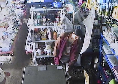 CCTV camera footage shows the suspect in the act of stealing a bag of cash from the shop.