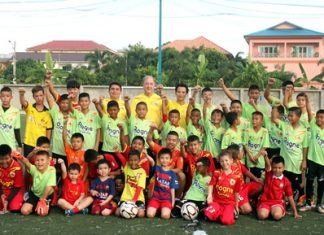 Ossi Schnieder, former coach of the Pattaya United (centre rear), poses with the young soccer students at the Palladium football field off, Soi Korphai, January 21.
