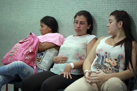 In this Thursday, Feb. 11, 2016 file photo, Daniela Rodriguez, 19, six-weeks pregnant, sits between two other women who are expecting, as they wait for test results after being diagnosed with the Zika virus at the Erasmo Meoz Hospital in Cucuta, Colombia. (AP Photo/Ricardo Mazalan)