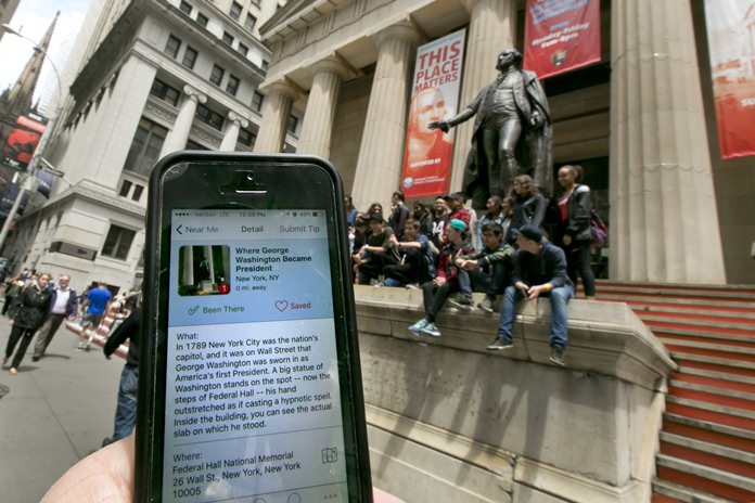 In this Tuesday, May 24, 2016, photo, the Roadside Presidents smartphone app directs people to the statue of George Washington on the steps of the Federal Hall National Monument, in New York's Financial District. Heading out for a holiday weekend road trip? There are a number of apps available to entertain and educate along the way. (AP Photo/Richard Drew)