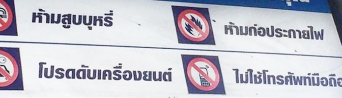 A sign indicating the 4 rules in a gas station: 1) No smoking, 2) No using lighters 3) Turn off engines while filling gas, 4) No mobile phones while filling gas.
