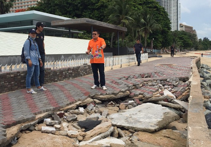 Deputy Mayor Verawat Khakhay inspects pavement and bricks along a walkway at Wong Amat Beach that sustained heavy damage from recent storms.