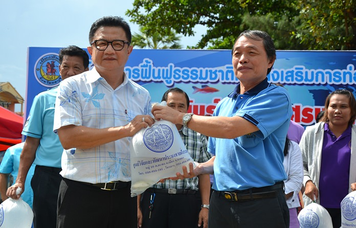 Jaroen Reunghataidhamma (right), director of the Rayong Coastal Fisheries Research and Development Center, presents fish to Deputy Mayor Wutisak Rermkitkarn on the occasion of World Environment Day.
