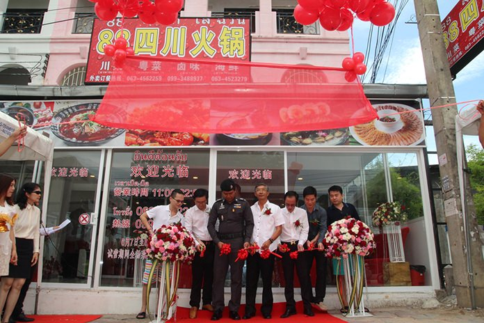 Pol Maj Saranyapong Maithongkulthorn (3rd right) cuts the ceremonial ribbon with Liu Songbai (4th right) and his team during the grand opening.