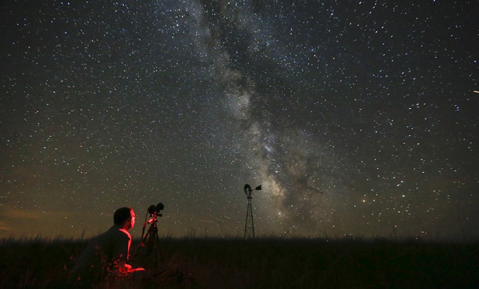 In this Wednesday, July 23, 2014 file photo, Omaha photographer Lane Hickenbottom photographs the night sky in a pasture near Callaway, Neb. With no moon in the sky, the Milky Way was visible to the naked eye. More than one-third of the world's population can no longer see the Milky Way because of man-made lights, according to a scientific paper by Light Pollution Science and Technology Institute's Fabio Falchi and his team members, published on Friday, June 10, 2016. (Travis Heying/The Wichita Eagle via AP)