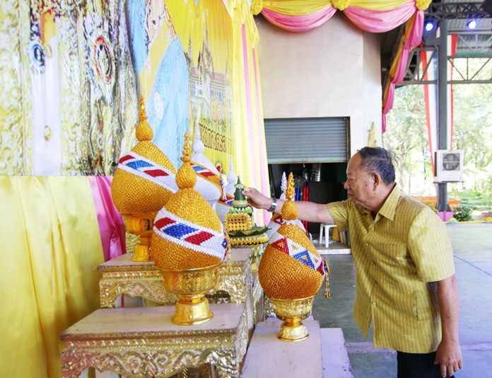 Nongprue Mayor Mai Chaiyanit presents flower cones before a portrait of His Majesty the King.