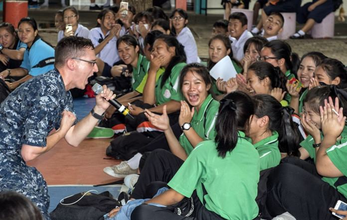 """Pattaya (June 21, 2016) Musician 3rd Class Holden Moyer from the 7th Fleet Rock Band """"Orient Express"""" sings with students during a joint rock concert with the Royal Thai Marine Corps Band at Photisampan School in support of Cooperation Afloat Readiness and Training (CARAT) Thailand 2016."""