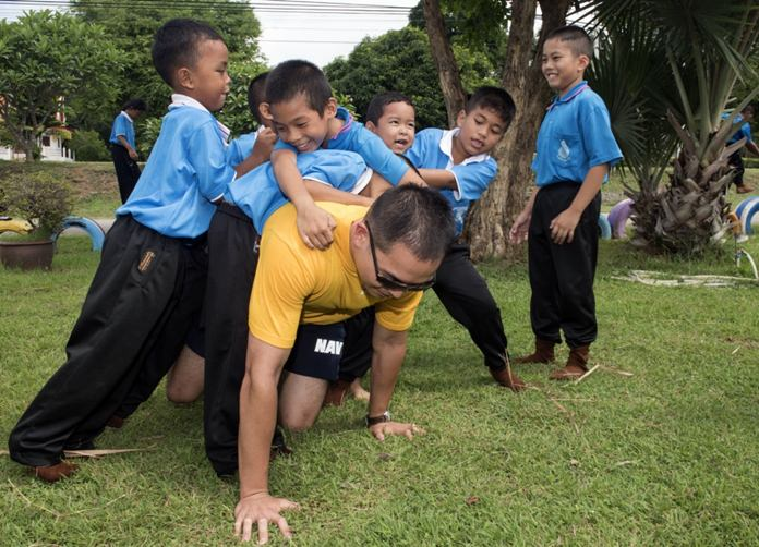 Sattahip (June 22, 2016) Ensign Terence Viernes is dog-piled by children from Chuksamet School. (U.S. Navy photo by Mass Communication Specialist 2nd Class Joshua Fulton/Released)