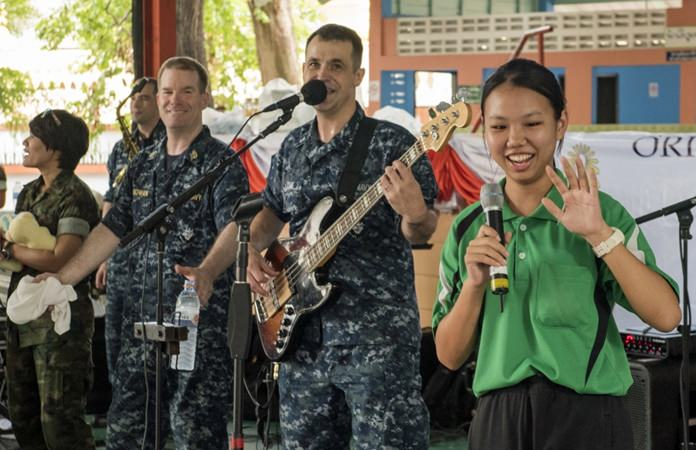 """Pattaya (June 21, 2016) The U.S. Navy 7th Fleet Rock Band """"Orient Express"""" invites a student from the Photisampan School to sing a local song during a joint rock concert with the Royal Thai Marine Corps Band. (U.S. Navy photo by Mass Communication Specialist 2nd Class Joshua Fulton)"""