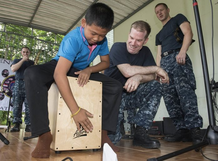 """Sattahip (June 22, 2016) The 7th Fleet Rock Band """"Orient Express"""" teaches a student from Chuksamet School how to play a cajon box drum during a concert there. (U.S. Navy photo by Mass Communication Specialist 2nd Class Joshua Fulton/Released)"""