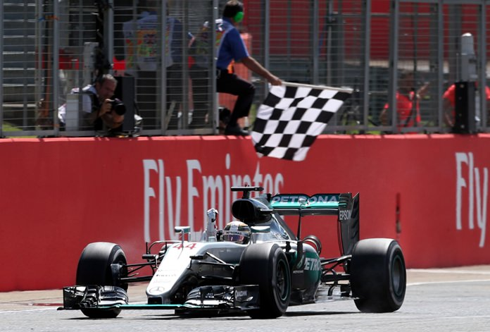 Mercedes driver Lewis Hamilton of Britain crosses the finish line to win the British Formula One Grand Prix at the Silverstone racetrack, Silverstone, England, Sunday, July 10. (David Davies/PA via AP)