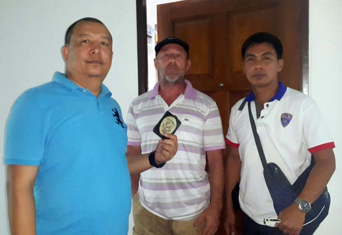 Andrew Ronald Matthews (center) was taken into custody by Chonburi immigration police at his View Talay condominium in Jomtien Beach on charges of defaming and harassing Thai nationals online.