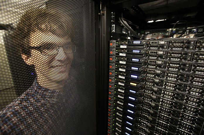 """In this Wednesday, June 22, 2016, photo, Massachusetts Institute of Technology researcher Carl Vondrick looks through a protective door while standing next to a computer server cluster, right, on the MIT campus, in Cambridge, Mass. MIT says a computer that binge-watched TV shows such as """"The Office,"""" """"Big Bang Theory"""" and """"Desperate Housewives"""" learned how to predict whether the actors were about to hug, kiss, shake hands or slap high-fives, a breakthrough that eventually could help the next generation of artificial intelligence function less clumsily. (AP Photo/Steven Senne)"""