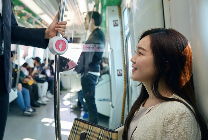 """In this Wednesday, April 6, 2016 photo provided by Busan Metropolitan City, a woman sits on special priority seats next to a metal bar attached with a """"pink light"""" wireless sensor in a subway train in Busan, South Korea. South Korea's second-largest city of Busan is testing a wireless technology it hopes can alleviate such problems and perhaps help address one of the biggest challenges facing the Asian country: a stubbornly low birthrate. (Kwon Sung-hoon/Busan Metropolitan City via AP)"""