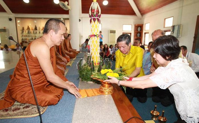 Interim Pattaya Mayor Chanatpong Sriviset and local officials present candles and offerings to monk at Wat Chonglom in Naklua.