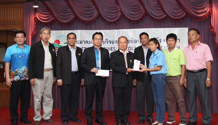 Pattaya City Council Chairman Anan Angkanawisai, PBTA President Sinchai Wattanasartsathorn, Pattaya Baht Bus Association Chairman Tawat Phuakboonnak, and honorable guests present a plaque to baht bus driver Duangjai Namchiang to thank her for her honesty.